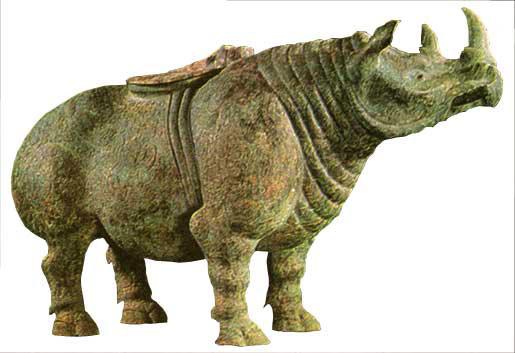青铜制,战国时期制作,出土于陕西兴平县。 春秋战国时期的动物雕塑以创作形象上的自由、生动而著称,并取得了巨大成就。当时的动物雕塑大量出现在日用品中,犀尊就是当时一种比较典型的盛酒器。从商代到战国,人们把犀牛和象视为神奇的动物,并创作了很多带有犀牛或象等形象的酒器,被称为犀尊或象尊。这种酒器一般背上有盖,顶端的左侧伸出一根细管以便倒酒。这件在兴平出土的《青铜犀尊》就是其中最精彩的作品。 这只犀牛形象雄健,体态逼真。它的头部平抬,上面长有双角,四只短腿粗壮结实,有力地支着沉重的躯体,使整个形像如同一座伸出悬岩
